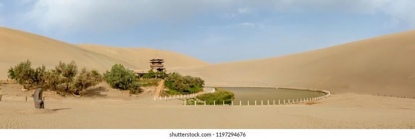 Panorama of pagoda on shores of Crescent Lake at Singing Sand Mountain dunes of Taklamakan Desert, Dunhuang, China.