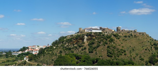 Panorama of Palmela castle longest view on the top of the hill. Partial view of the historical village hiding behind it. Blue sky with clouds. Setubal disctrict, Portugal.