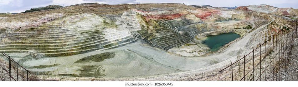 A panorama or a panoramic view of calcium bentonite quarry, located in the area of a bentonite processing plant in Greece. At the bottom of the quarry  is clearly seen water coming here from a sea.