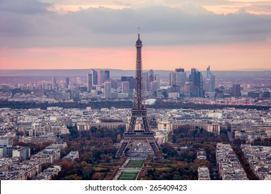 A panorama of Paris at a sunset. A view of the Eiffel Tower, the Defence quarter, of the urban neighborhoods from the bird's-eye view. The sky is clouded over.