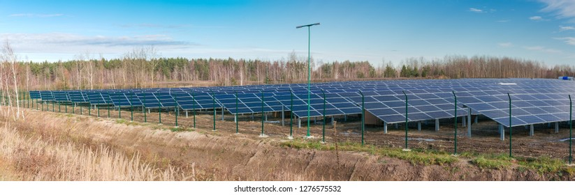 Panorama of part of ground-mounted solar power station with fixed photovoltaic panels on a background of sky and forest at late autumn