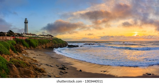 Panorama with pastel colors of sunset and silky water from long exposure of waves crashing on the shore by Pigeon Point Lighthouse on Northern California Pacific Ocean coastline near Pescadero