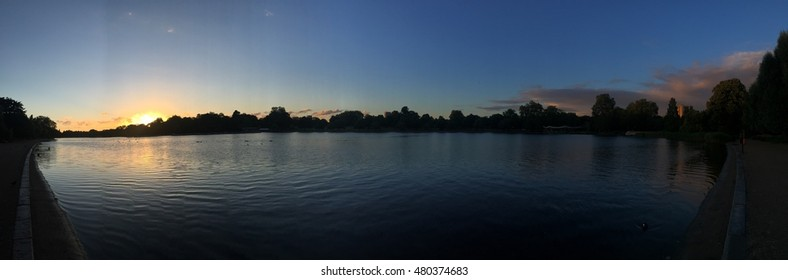 Panorama photo of Hyde Park, Serpentine Lake with a striking sunset