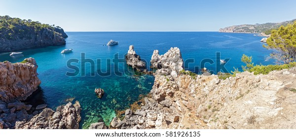 Panorama Photo of the open sea. Three yachts go to the open sea of Mallorca, Spain, transparent water and cliffs on the coast.