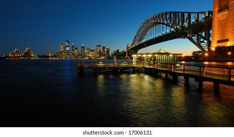 panorama photo of sydney cbd, opera house and harbour bridge during sunset
