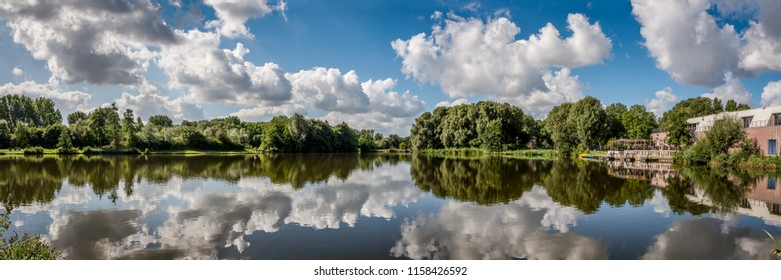 Panorama photo of typical Dutch clouds above the water of Westerpark in Zoetermeer.