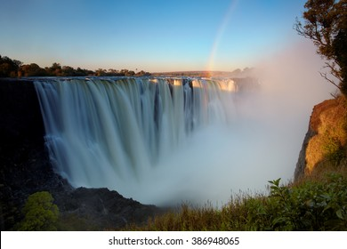 Panorama photo of  Victoria Falls or Mosi-oa-Tunya, waterfall on Zambezi river in very high flow from viewpoint 5  in late evening light with rising spray and intensive rainbow over falls.