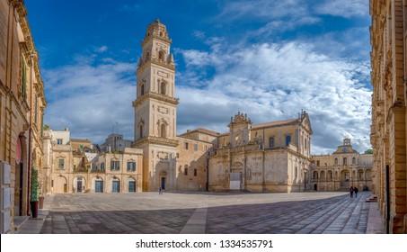 Panorama of Piazza del Duomo square , Campanile tower and Virgin Mary Cathedral ( Basilica di Santa Maria Assunta in Cielo ) , Caritas Diocesana in Lecce - Puglia, Italy. Baroque city of Apulia