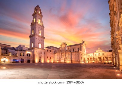 Panorama of Piazza del Duomo square , Campanile tower and Virgin Mary Cathedral ( Basilica di Santa Maria Assunta in Cielo ) , Caritas Diocesana in Lecce - Puglia, Italy. Baroque city of Apulia sunset