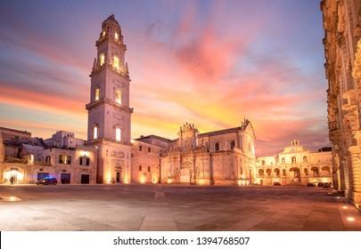 Panorama of Piazza del Duomo square, Campanile tower and Virgin Mary Cathedral (Basilica di Santa Maria Assunta in Cielo), Caritas Diocesana in Lecce - Puglia, Italy. Baroque city of Apulia sunset