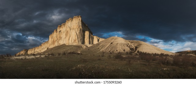 Panorama of picturesque mountain landscape at sunset with  heavy dark thunderclouds. Beautiful White Rock in the rays of the setting sun before the storm. Copy space on the dark sky.