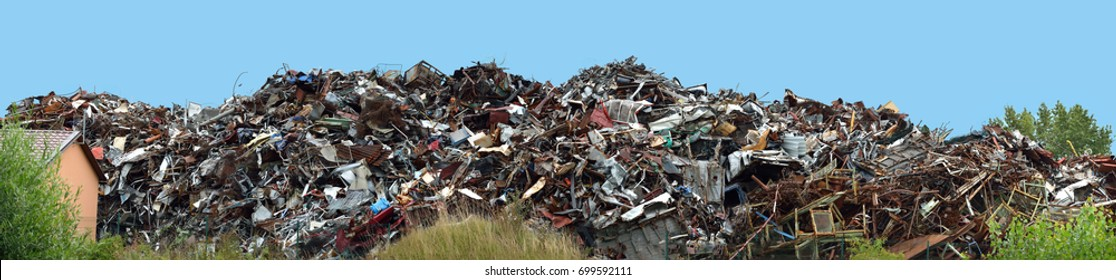 Panorama of a pile of scrap metal with a blue sky