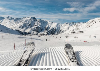 Panorama point of view skier legs on downhill start straight line rows freshly prepared groomed ski slope piste on bright day blue sky background. Snowcapped mountain landscape europe winter resort