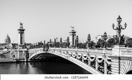 Panorama of the Pont Alexandre III bridge over the River Seine and the Hotel des Invalides in the morning. Bridge decorated with ornate Art Nouveau lamps and sculptures. Paris, France. Black and white