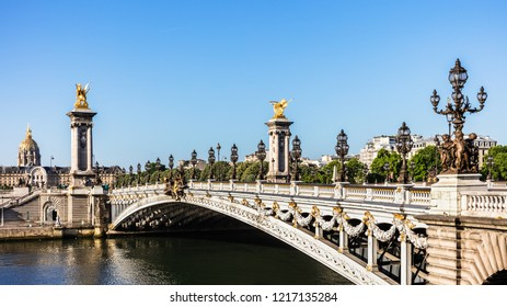 Panorama of the Pont Alexandre III bridge over the River Seine and the Hotel des Invalides in the summer morning. Bridge decorated with ornate Art Nouveau lamps and sculptures. Paris, France.