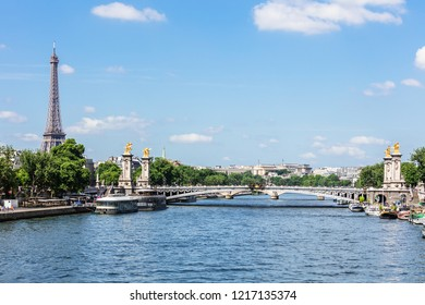 Panorama of the Pont Alexandre III bridge over the River Seine and the Eiffel Tower in the summer morning. Bridge decorated with ornate Art Nouveau lamps and sculptures. Paris, France