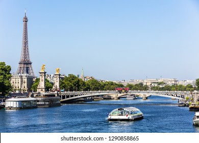 Panorama of the Pont Alexandre III bridge over the River Seine and the Eiffel Tower in the summer morning. Bridge decorated with ornate Art Nouveau lamps and sculptures. Paris, France.