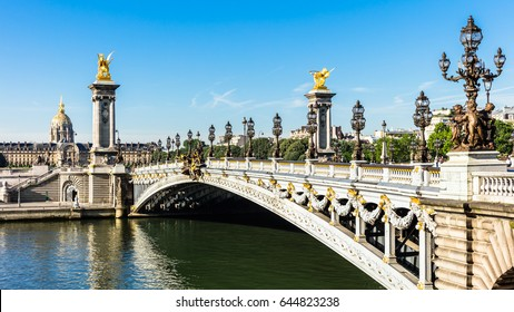 Panorama of Pont Alexandre III bridge over river Seine and Hotel des Invalides in the summer morning. Bridge decorated with ornate Art Nouveau lamps and sculptures. Paris, France