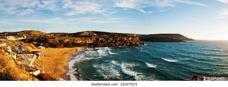 Panorama of the popular sandy beach of Golden Sand Bay, Malta awash in evening sunlight