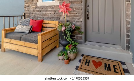 Panorama Porch of a home decorated with wooden chair potted plants wreath and doormat