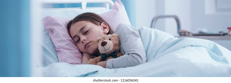 Panorama portrait of a sick little girl sleeping in a hospital bed with a teddy bear - view through the door