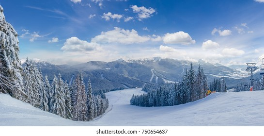 Panorama of the prepared ski slope among spruce forest on a background of mountain ranges and sky on ski resort in Carpathian Mountains