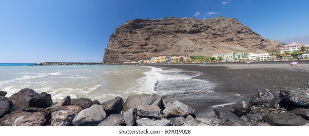 Panorama of Puerto Tazacorte with rocks in the foreground, beach and colorful houses, La Palma, Canary Islands, Spain