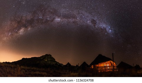 A panorama of the purple magic milky way and a sky full of stars above a little African hut which is shining in orange light with a little hill in the background and more houses in the back