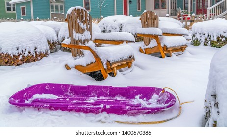 Panorama Purple sled and wooden chairs surrounded by snow during winter in Daybreak