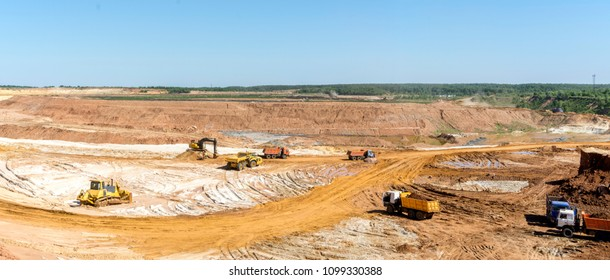 Panorama of the quarry. Extraction of sand in the quarry. Backhoe loading sand into dump trucks.
