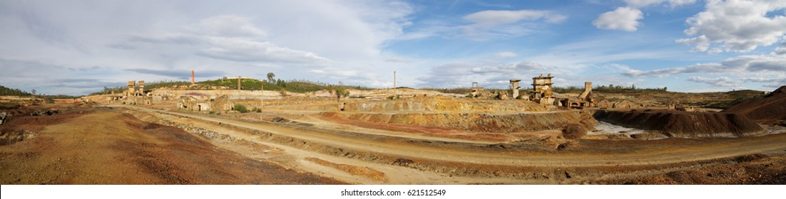 Panorama of the railway path turned into road at Achada do Gamo before Sao Domingos mine abandoned sulfur extraction ovens and fields of scoria. Blue clouded sky. Mertola, Alentejo, Portugal.