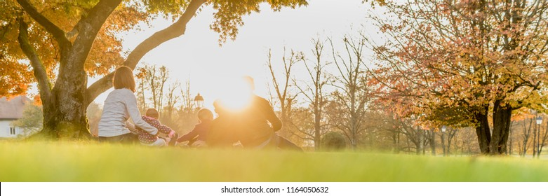 Panorama rear view of young family with three kids enjoying a day together backlit by a beautiful evening sun.