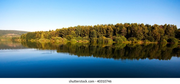 Panorama and reflection of the forest in the mountain lake