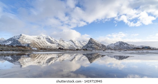 Panorama reflection of snowy mountains, blue sky and clouds on the calm clear water on a beach. A range of pointy mountain in beautiful winter landscape of Lofoten in northern Norway. Desolated land.