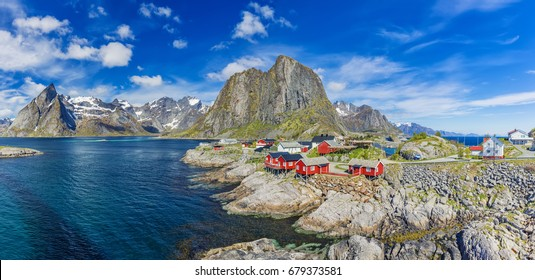 Panorama Of Reine On The Lofoten In Northern Norway. The Typical Norwegian Fishing Village Of Reine With The typical Rorbu Houses At Sunny Day, Mountain In Background