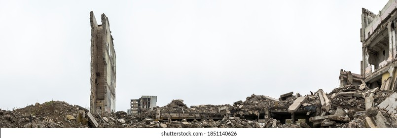 Panorama. The remains of a building with piles of gray concrete rubble and a detached ruined wall against a hazy sky. Background.