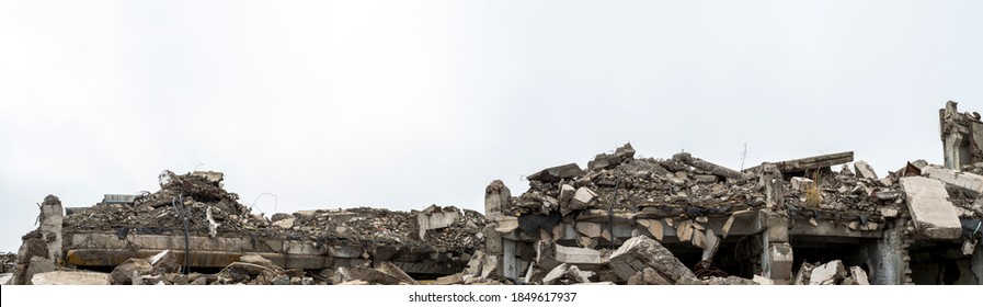 Panorama of the remains of a destroyed building, piles of concrete debris and construction debris against a neutral gray sky in a foggy haze. Background.