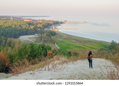 Panorama of the resort town of Nida on the Curonian Spit. A tourist photographs a view of Nida from the highest dune.