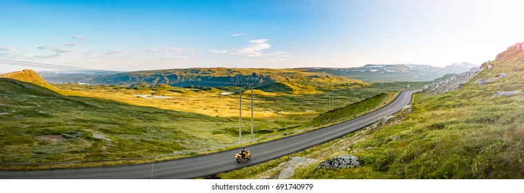 Panorama of road with bike. Nature in Norway. Blue cloudy sky and mountains. Nordic country. Europe travel, scandinavia.
