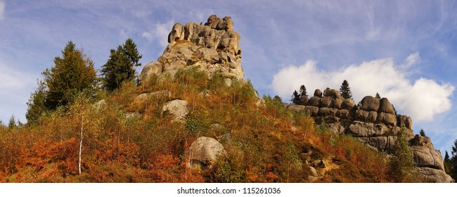 Panorama rocks against the blue sky and autumn forest