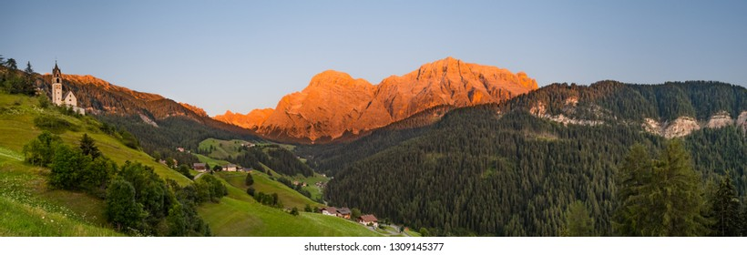 Panorama of rocky mountain peaks lit by sunset with a church on green hill in the Dolomites, in La Valle, South Tyrol, Italy.