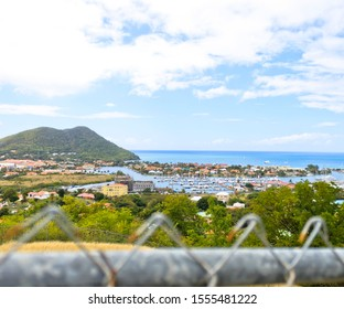 Panorama of Rodney Bay Marina, the tranquil inviting Caribbean sea, bright blue cloudy sky on a sunny day,  clay roof, orange tin roofs,  Bonne terre with greenery and natural beauty beyond a fence