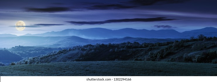 panorama of romania countryside at night in full moon light wonderful springtime landscape in mountains. grassy field and rolling hills. rural scenery