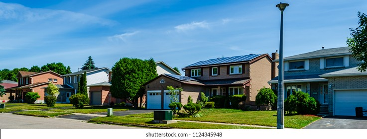 Panorama of a row of residential houses along a street, one with solar panels on the roof under a blue sky