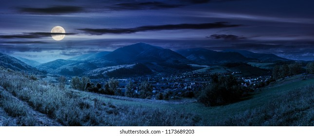 panorama of rural fields on curvy slopes. bright autumn day. lovely countryside at night in full moon light. village down in the valley. gorgeous cloudscape above mountain ridge in the distance