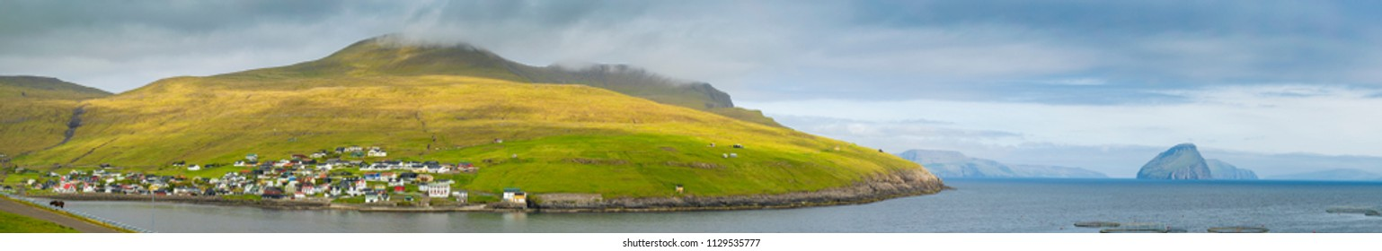 Panorama of Sandavagur, Faroe Islands (Faroes), Salmon farm rings floating on calm water, Atlantic Ocean, Denmark, Europe