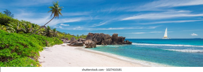 Panorama of sandy beach with beautiful rocks, palms and a sailing boat in the turquoise sea on Paradise island.