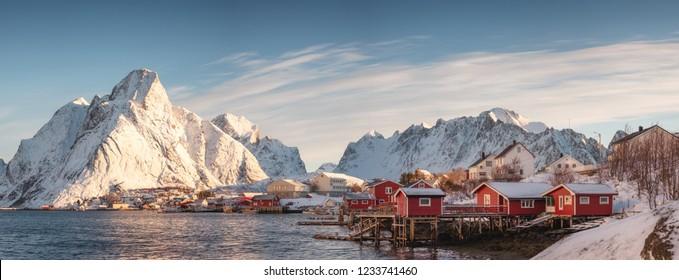 Panorama of Scandinavian village with snow mountain at coastline in morning. Lofoten islands, Norway