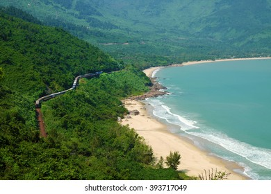 Panorama scene of Lang Co beach, Hue from Hai Van mountain pass at Da Nang, Viet Nam. Amazing landscape of train moving on railway at seaside, nice view of nature with green forest, wave on sea