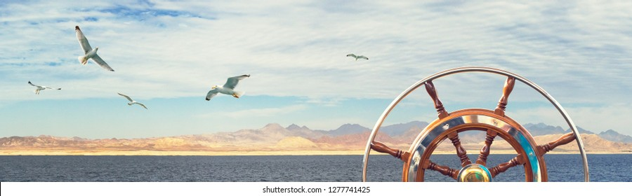 Panorama of sea landscape with steering wheel on the sailboat for your concept of marine adventure or sea cruise. Skyline with rocky coast, cloudy sky and flying seagulls over the sea, wide format.